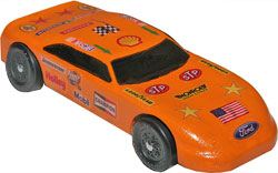 NASCAR pinewood derby car painted orange with NASCAR decals